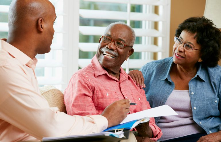 Financial Advisor Talking To Senior Couple about retirement At Home Showing Documents Smiling