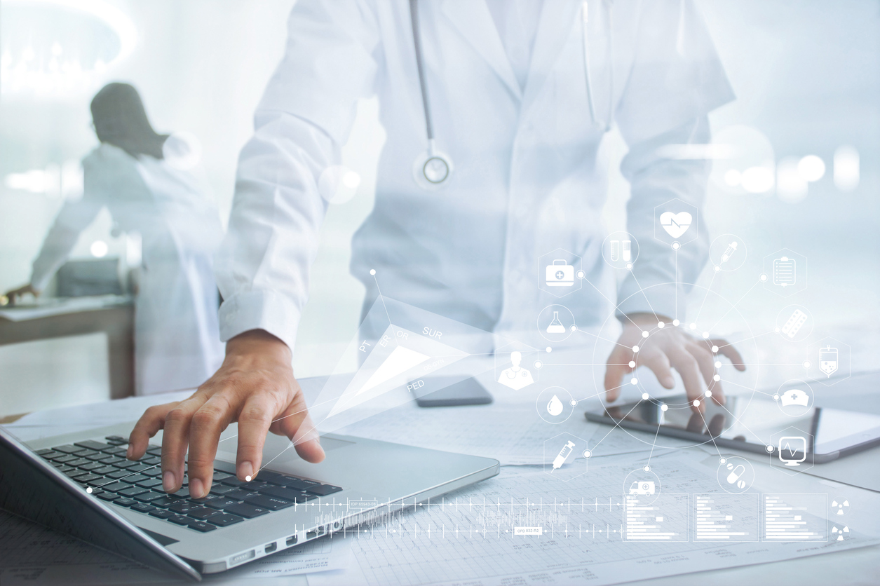doctor-using-laptop-and-tablet-with-digital-icons-floating-over-tablet